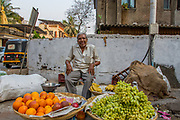 India, Uttar Pradesh, Varanasi, happy smiling mature street vendor selling fruit in the market