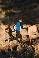 A male athlete runs along the Red Rocks Trail in the foothills of the Rocky Mountains near Boulder, Colorado