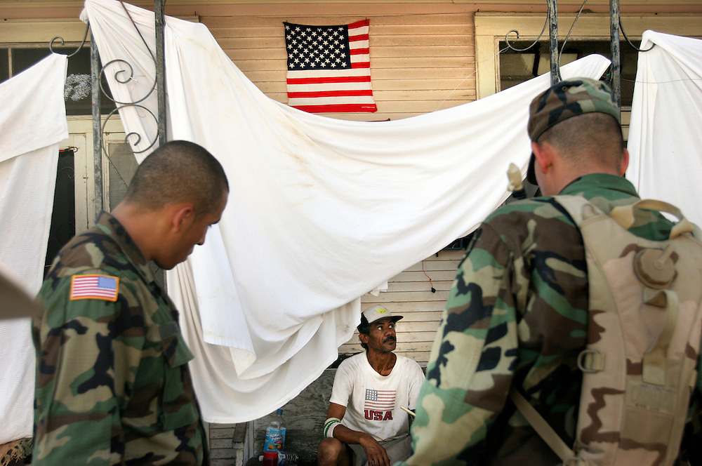 Spec. Roberto Gomez and PFC Donald Epperson check up on survivor John Daigle, unwilling to leave even though floodwaters surround his house and reach three steps up his stoop, and even though New Orleans is under mandatory evacuation. Oregon National Guard troops work in New Orleans after the wrath of Hurricane Katrina. Photographed September 8, 2005. (Thomas Patterson / Statesman Journal) The soldiers are with the 1186th Military Police.
