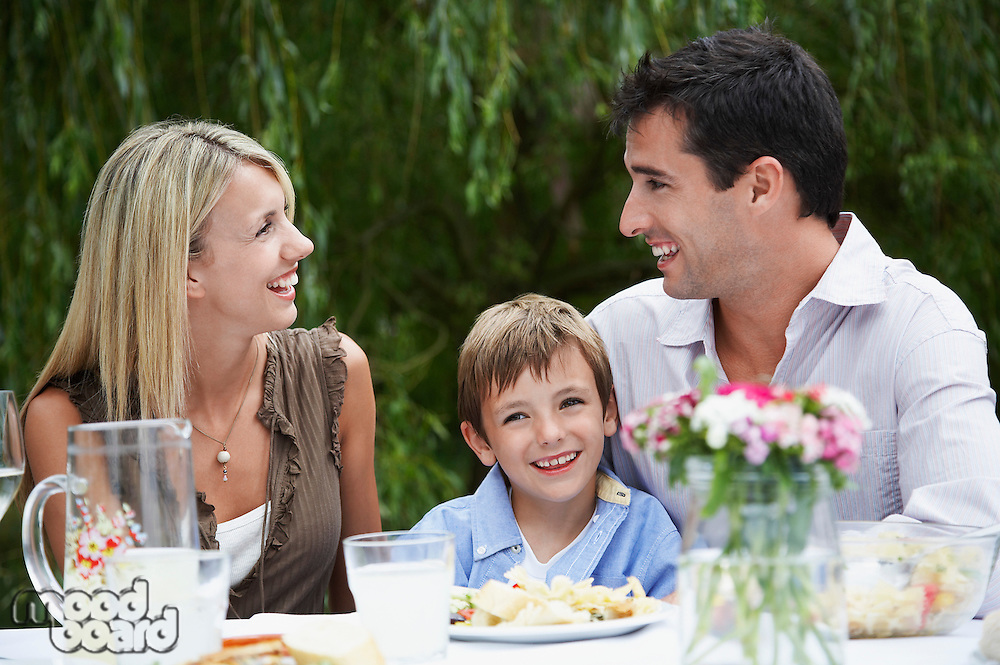 Couple with son (7-9) sitting at table in garden