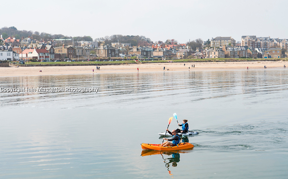 Couple in canoes off beach at North Berwick in East Lothian, Scotland, United Kingdom