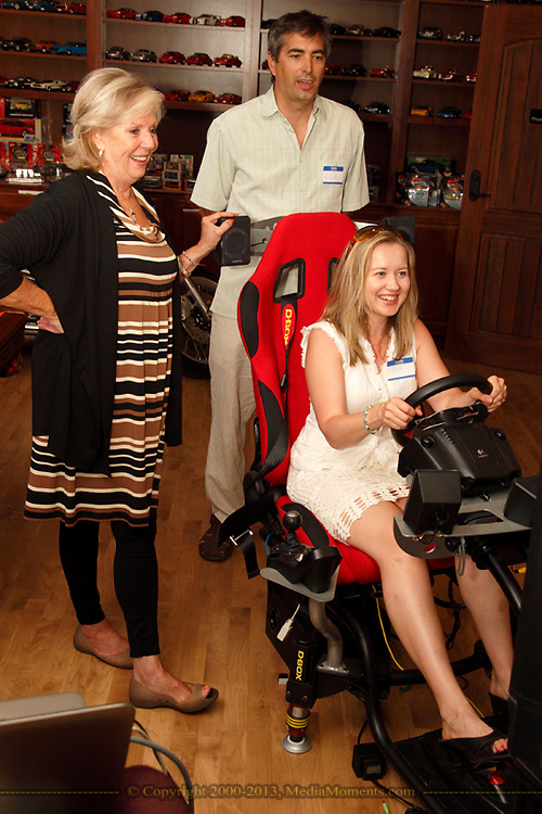 (from left) Jeanne Porter of WiBN and Richard Lamm of Tim Horton's  watch Julia Lamm of Tim Horton's experience the race car simulator during a Women in Business Networking After 5 event at Audio Etc... in Centerville, Thursday, August 30, 2012.
