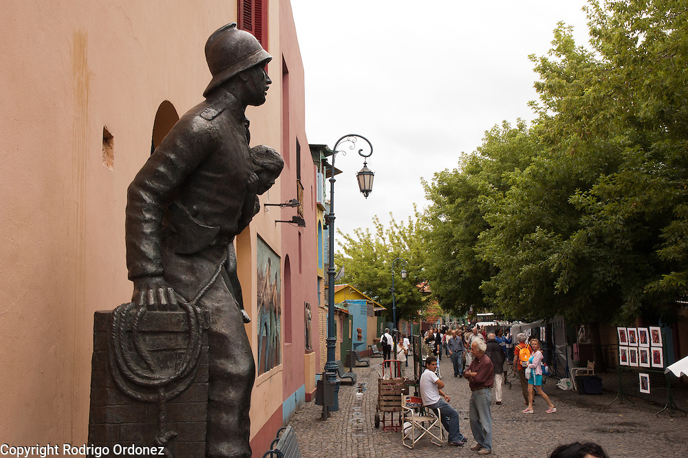 Monument to the Volunteer Firefighter, by Ernesto Scaglia, in Caminito street, in La Boca neighborhood of Buenos Aires, Argentina.<br /> Caminito is a pedestrian street created in the late 1950s by local painter Benito Quinquela Mart&iacute;n and other artist friends to recreate a version of the old immigrant neighborhood of La Boca, using wood and corrugated zinc painted in bright colors. Today, Caminito and the surrounding areas feature cafes, souvenir shops, tango dancers and other street performances aimed to attract tourists.