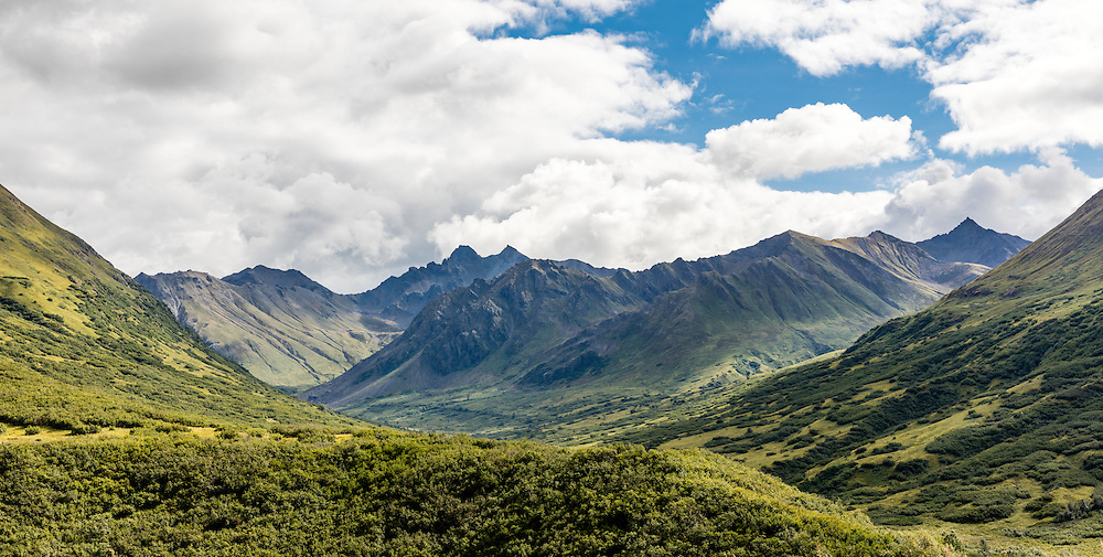 Scattered clouds provides a mix of highlights and shadows on the Talkeetna Mountains surrounding Mint Glacier Valley in Hatcher Pass in Southcentral Alaska. Summer. Morning.