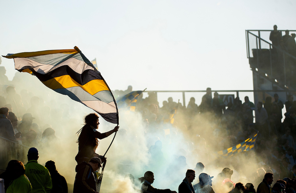 A Philadelphia fan in the Sons Of Ben supporters section waves a flag against a smoky backdrop to celebrate Philadelphia's 1-0 win. <br /> Philadelphia Union vs. New England Revolution at PPL Park in Chester Pennsylvania. March 15, 2014.<br /> <br /> (Jack Megaw/www.jackmegaw.com)<br /> <br /> <br /> <br /> &copy;Jack Megaw, 2014. <br /> ALL RIGHTS RESERVED. NO UNPAID USE.