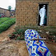 15/4/05 - Ganacamana, Angola - WHO doctors and workers disinfect and place the body of Marburg victim Louiza Nevish Bati, 23, in a coffin in the village of Ganacamana on the outskirts of Uige.