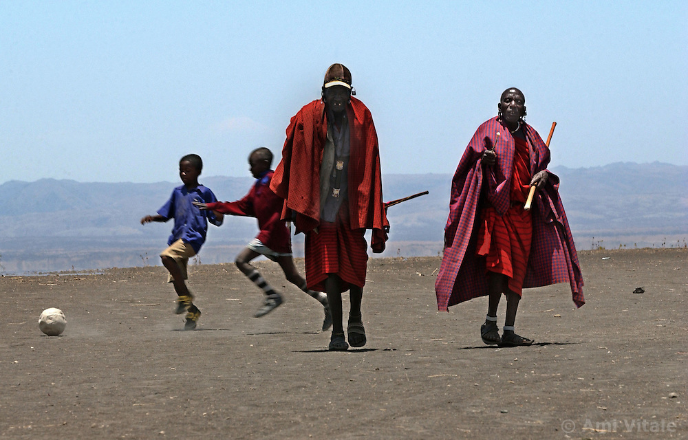 The signs of changing times are evident as Maasai children relax with a game of football as their elders walk by cloaked in traditional clothing during lunch break at the Endulen Primary school in Ngornogoro District in Tanzania September 29, 2003.  Most Maasai now see the value of sending their children to school so they can have a voice in the government to protect themselves with increasing land loss. The Maasai were thrown out of the Crater in 1972 in the name of conservation and are being threatened again  under a torrent of new legislation. Like other indigenous people the world over, they continue to be evicted from their land in the name of tourism and conservation. They have lived on these lands for centuries but now struggle to survive on their borders, especially in the difficult drought years. Though they were able to live in harmony with the wildlife for centuries, the places with rich water sources are now preserved for tourists.  Eco-tourism, the government solution to chronic poverty, brings in vast revenues but sadly, the dispossessed Maasai are not allowed to benefit. Only a handful, mostly foreign owned tourist operators profit and only a tiny portion of the money actually filters through to the local economy. (Photo by Ami Vitale/Getty Images)