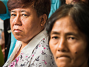 10 SEPTEMBER 2015 - BANGKOK, THAILAND:  Women watch as demolition crews wreck Chaiyasit Kittiwanitchapant's home. Authorities started to destroy 54 homes in front of Wat Kalayanamit, a historic Buddhist temple on the Chao Phraya River in the Thonburi section of Bangkok. Government officials, protected by police, seized the house of Chaiyasit Kittiwanitchapant, a Kanlayanamit community leader, who has led protests against the temple's abbot for trying to evict community members whose houses are located around the temple. Work crews went into Chaiyasit's home and took it apart piece by piece. The abbot of the temple said he was evicting the residents, who have lived on the temple grounds for generations, because their homes are unsafe and because he wants to improve the temple grounds. The evictions are a part of a Bangkok trend, especially along the Chao Phraya River and BTS light rail lines, of low income people being evicted from their long time homes to make way for urban renewal.    PHOTO BY JACK KURTZ