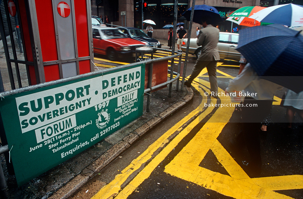In the days before the historical Handover of sovereignty of Hong Kong from Britain to China, a banner calls for a Democracy rally in two locations, on 27th June 1997, in Hong Kong, China. (Photo by Richard Baker / In Pictures via Getty Images)