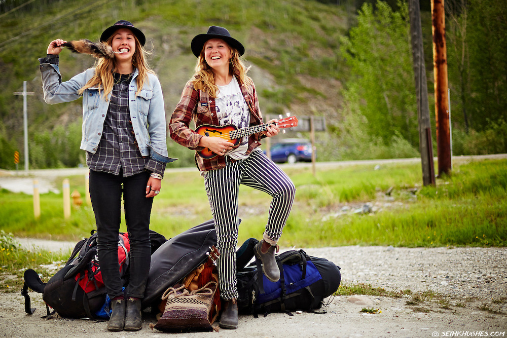 Two spirited young women stand alongside a highway hitchhiking on the Klondike Highway in Yukon Territory, Canada.