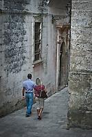 Siamo in Puglia, a Specchia cittadina della provincia di Lecce, situato a circa 60 Km a sud del capoluogo di provincia..Si presenta come un paese tranquillo ma vivo..Le strade luminose e pulite presentano una pavimentazione a lastroni antichi..Il centro storico è un'area pedonale ed è spesso scenario di manifestazioni sacre e culturali..La gente è gentile ed ospitale e si è lasciata fotografare con tranquillità, facendosi riprendere nel loro fare quotidiano, quasi fosse abituata ad essere fotografata..Quest'area del Salento è meta di un turismo alla ricerca della tranquillità e della cultura; cultura intesa anche come eno-gastronomia, e soprattutto cultura volta al rispetto della natura..I turisti in cerca di aria sana, pulita, vengono nei paesini dell'entroterra salentino, lontani dalla città e dallo smog..Appena entrati in paese ci si ritrova una piazzetta moderna, molto ben concepita architettonicamente, sulla quale si affacciano anche palazzi di età più antica, probabilmente dell'inizio del '900...La piazza e le strade nei dintorni sono animate dalla popolazione, che approfitta del primo fresco del pomeriggio per uscire a stare in compagnia..Gente del posto, anziani in prima linea vivono la piazza, ragazzi passeggiano e visitano il palazzo e le attività commerciali..Passeggini e biciclette percorrono le strette vie del borgo, qua e là la gente fa capolino e si appresta a uscire a ritirare i panni o a far visita al vicino.