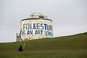 A man play golf in front of a Folkestone is an Art School banner, attached to Folkestone's most prominent Martello Tower on the east cliff. The banner has been designed by the artist Bob and Roberta Smith as part of the 2017 Folkestone Triennial. Folkestone, Kent.(photo by Andrew Aitchison / In pictures via Getty Images)