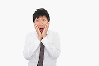 Shocked mid adult businessman with hands on face over white background