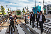 """Pedestrians walk over a crossing in front of a tram on the Toden Arakawa Line in Tokyo, Japan Friday October 12th 2012. Nick-named the """"Chin-chin"""" Densha"""" after the sound it bell used to make the Toden Arakawa Line is the last tram-line in Tokyo."""