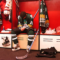 Wearing a specially made green St. Patrick's day uniform, Jason Krispel rests in the locker room during the first period break with the score 1-1 against the Helena Big Horns. The Icedogs broke away from Helena in the third period winning 5-4. .