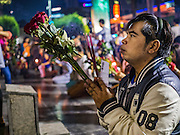 18 FEBRUARY 2016 - BANGKOK, THAILAND:  A man prays, holding nine red roses and sticks of incense, at the Trimurti Shrine in Bangkok. Every Thursday night, starting just after sunset and peaking at 21.30, hundreds of Bangkok single people, or couples seeking guidance and validation, come to the Trimurti Shrine at the northeast corner of Central World, a large Bangkok shopping mall, to pray to Lord Trimurti, who represents the trinity of Hindu gods - Brahma, Vishnu and Shiva. Worshippers normally bring an offering of red flowers, fruits, one red candle and nine incense sticks. It's believed that Lord Trimurti descends from the heavens at 21.30 on Thursday to listen to people's prayers. Although most Thais are Buddhists, several Hindu traditions have been incorporated into modern Thai Buddhism, including reverance for Trimurti.      PHOTO BY JACK KURTZ