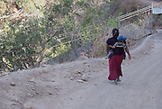 A woman walks with a boy in her back on the road in Juanacatlán, Guerrero  on April 16th, 2010.  (Photo: Prometeo Lucero)