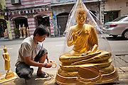"05 JULY 2011 - BANGKOK, THAILAND:     A man wraps a Buddha statue in clear plastic before putting it on sale in his store on Bamrung Muang Street in Bangkok. Thanon Bamrung Muang (Thanon is Thai for Road or Street) is Bangkok's ""Street of Many Buddhas."" Like many ancient cities, Bangkok was once a city of artisan's neighborhoods and Bamrung Muang Road, near Bangkok's present day city hall, was once the street where all the country's Buddha statues were made. Now they made in factories on the edge of Bangkok, but Bamrung Muang Road is still where the statues are sold. Once an elephant trail, it was one of the first streets paved in Bangkok, it is the largest center of Buddhist supplies in Thailand. Not just statues but also monk's robes, candles, alms bowls, and pre-configured alms baskets are for sale along both sides of the street.        PHOTO BY JACK KURTZ"
