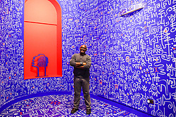 "© Licensed to London News Pictures. 09/06/2019. London, UK. New York based artist Victor Ekpuk poses for photographers within his hand painting artwork in a new exhibition ""Get Up, Stand Up Now"" at Somerset House, London. The exhibition opens on 12 June and runs until 15 September 2019. Photo credit: Dinendra Haria/LNP"