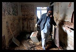 21st, December 2005. New Orleans, Louisiana. Armand Devezin clears his grandfathers' devastated, mould filled house in the 9th Ward long after the  flood from Hurrican Katrina subsided. The house has only recently been refurbished and has seen water to the ceilings before when Hurricane Betsy hit in the 1960's.