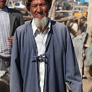 A religious man with hat and beard, holding his goat by its horns at a camel market, Turkmenistan