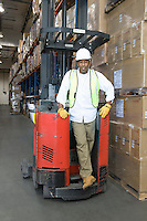 Man standing with fork lift truck in distribution warehouse