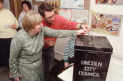 Carer assisting woman with learning difficulties to vote in local elections,