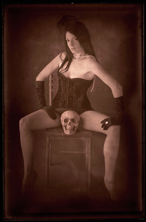 A young woman with long black hair dressed in a basque sitting on a chair with a skull between her legs