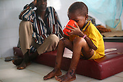 Abubakar Barrie, 8, a severely malnourished child, drinks up under the watch of his father Chernor Anhusine Barrie at the therapeutic feeding center of the Magbenthe hospital in Makeni, Sierra Leone on Thursday February 26, 2009. UNICEF sponsored some of the construction of the hospital facilities, and also provides high-protein biscuits and milk as part of a joint effort with the World Food Programme..