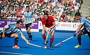 England's David Condon beats Pedro Ibarra and Ignacio Ortiz of Argentina. England v Argentina - Hockey World League Semi Final, Lee Valley Hockey and Tennis Centre, London, United Kingdom on 18 June 2017. Photo: Simon Parker