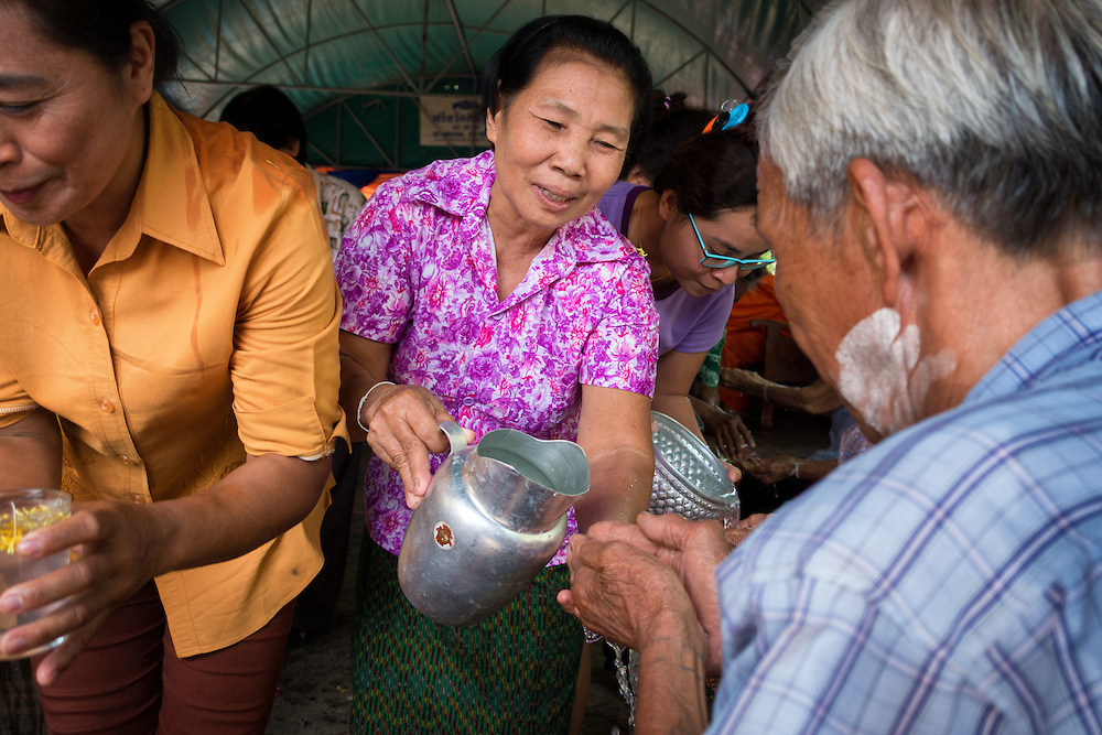 A Thai woman pours a water blessing over the hands of an elder as Songkran, is celebrated in rural Thailand.