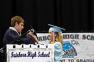 Kayla Hill, president of the Class of 2012 (right) helps Logan Snow, the prsident of the Class of 2013 get into his cap and gown during the Fairborn High School commencement at the Nutter Center in Fairborn, Friday, May 25, 2012.