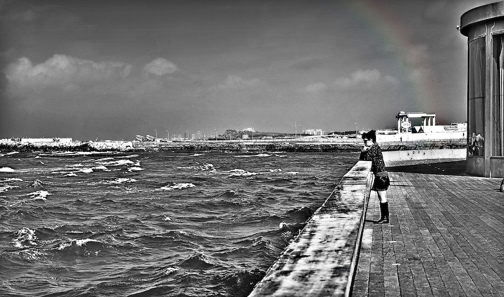 Rainbow and woman seafront
