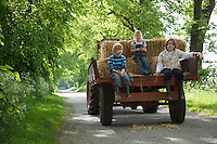 Three children (5-9) sitting on trailer on country lane