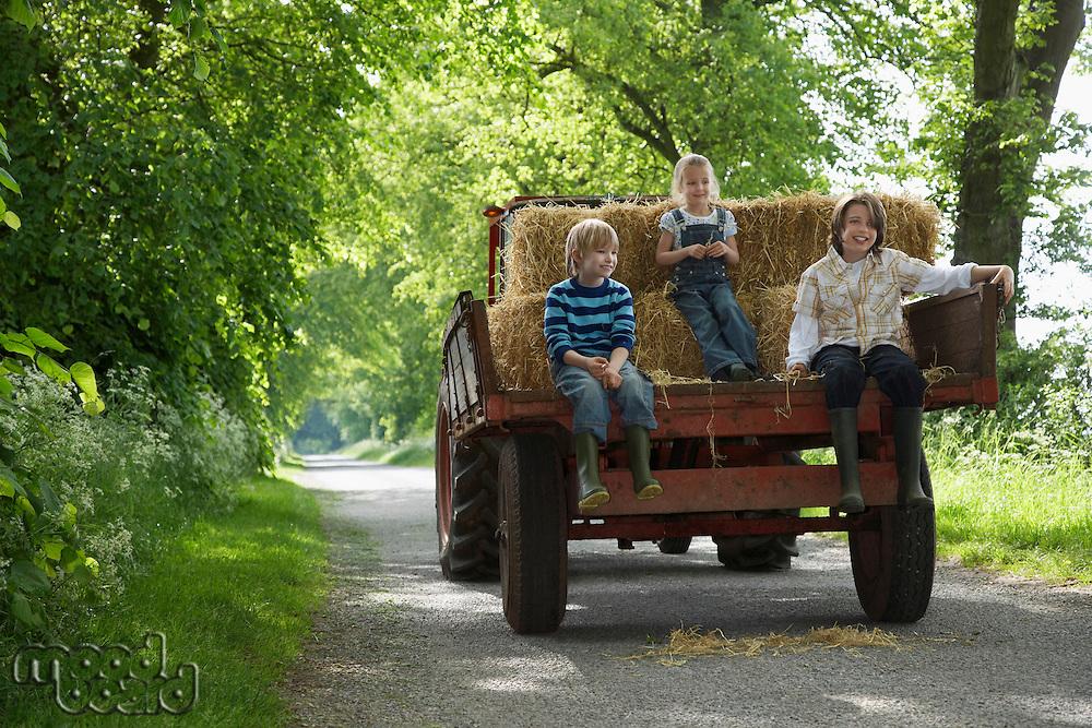 Three children (5-9) sitting on trailer on country lane
