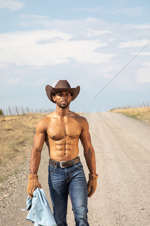 shirtless muscular cowboy on a dirt road