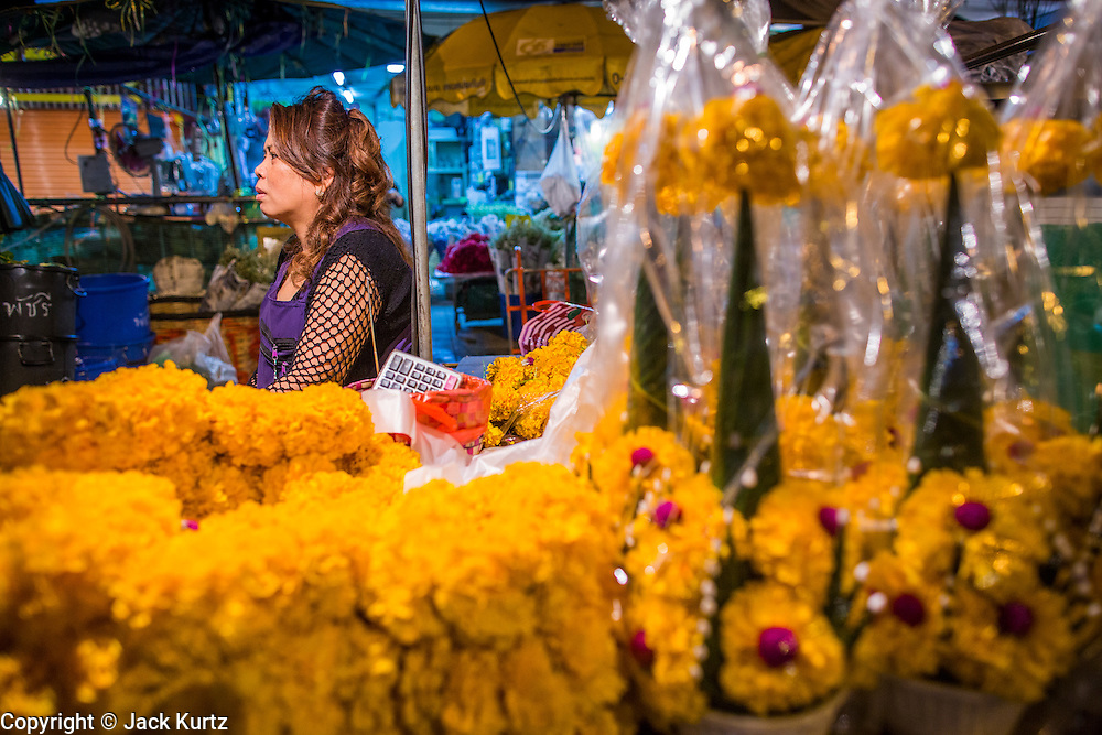 19 OCTOBER 2012 - BANGKOK, THAILAND:   A marigold vendor in the Bangkok Flower Market. The Bangkok Flower Market (Pak Klong Talad) is the biggest wholesale and retail fresh flower market in Bangkok.  The market is busiest between 3:30AM and 6AM. Thais grow and use a lot of flowers. Some, like marigolds and lotus, are used for religious purposes. Others are purely ornamental.       PHOTO BY JACK KURTZ