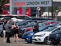 © Licensed to London News Pictures. 01/06/2020. London, UK. A salesman wearing a face mask shows members of the public cars on the forecourt of a car showroom in West London. Car showrooms are allowed to open today (Mon) after government introduced further measures to slowly ease lockdown, which was introduced to fight the spread of the COVID-19 strain of coronavirus. Photo credit: Ben Cawthra/LNP