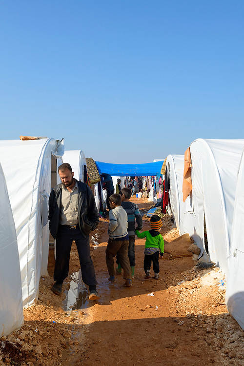 Syrian adults and children walk between a row of tents in the camp for displaced persons in Atmeh, Syria