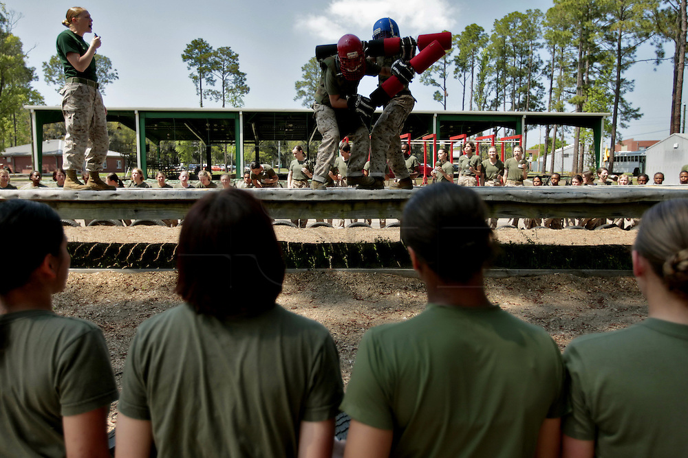 Female recruits look on as they prepare to engage in hand to hand combat training.  Marine Corps Recruit Depot at Parris Island in South Carolina is where all male recruits living east of the Mississippi River and all female recruits from all over the US receive their arduous twelve week training in their quest to become marines. Even though there are two current active wars and a weak economy, recruitment has not been effected.  Actually, recruiting numbers have increased, with more young men and women looking toward the military for answers.