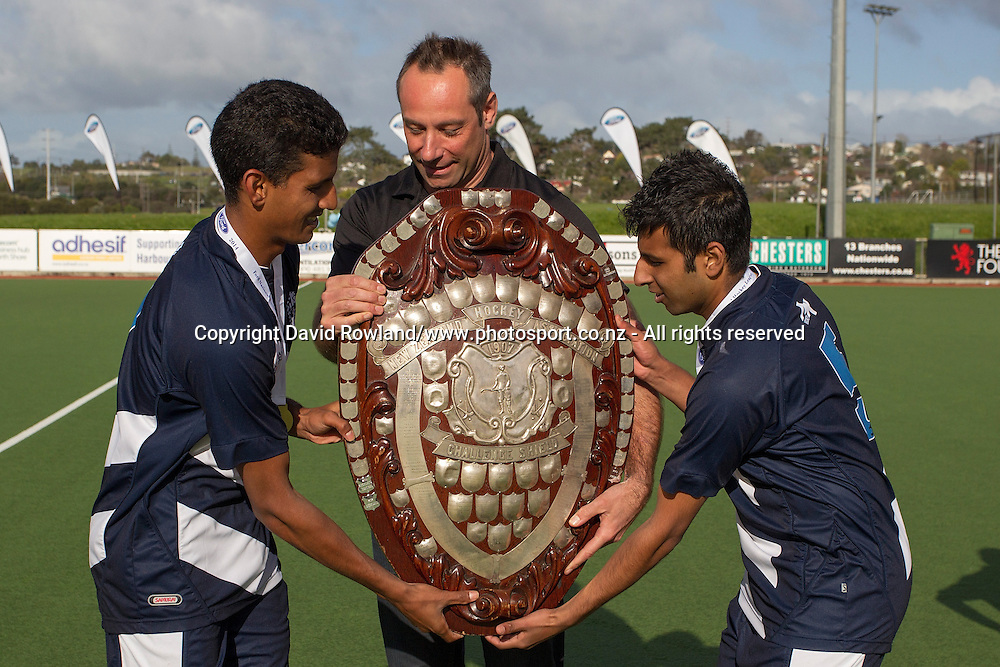 Ford Marketing Manager Chris Masterson presents the tournament winners trophy to Auckland co- captain`s Arun Panchia, left, and Ketan Hari after winning the Auckland v Midlands Men`s Final match, Ford National Hockey League, North Harbour Hockey Stadium, Auckland, New Zealand,Sunday, September 14, 2014. Photo: David Rowland/Photosport