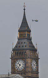 © Licensed to London News Pictures.23/03/2017.London, UK. A police helicopter passes behind Big Ben as Prime Minister Theresa May speaks to Parliament, the day after a lone terrorist killed 4 people and injured several more, in an attack using a car and a knife. The attacker managed to gain entry to the grounds of the Houses of Parliament, killing one police officer.Photo credit: Peter Macdiarmid/LNP