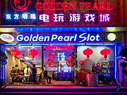 "13 FEBRUARY 2019 - SIHANOUKVILLE, CAMBODIA:  The Golden Peal Slot, a Chinese owned casino in Sihanoukville. There are about 80 Chinese casinos and resort hotels open in Sihanoukville and dozens more under construction. The casinos are changing the city, once a sleepy port on Southeast Asia's ""backpacker trail"" into a booming city. The change is coming with a cost though. Many Cambodian residents of Sihanoukville  have lost their homes to make way for the casinos and the jobs are going to Chinese workers, brought in to build casinos and work in the casinos.      PHOTO BY JACK KURTZ"