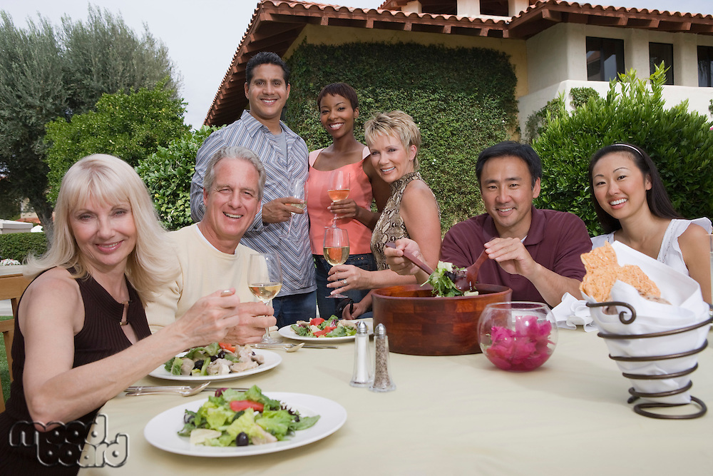 Group of friends dining outdoors portrait