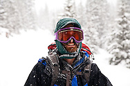 A skier smiles while touring to Peter Estin hut in a snow storm in Colorado. Telemark or AT skis with climbing skins are used to climb up steep snow slopes when doing backcountry skiing.