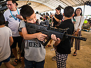 "14 JANUARY 2017 - BANGKOK, THAILAND: A child aims an empty Royal Thai Army  TAR-21 assault rifle during Children's Day activities at the King's Guard, 2nd Cavalry Division base in Bangkok. Thailand National Children's Day is celebrated on the second Saturday in January. Known as ""Wan Dek"" in Thailand, Children's Day is celebrated to give children the opportunity to have fun and to create awareness about their significant role towards the development of the country. Many government offices open to tours and military bases hold special children's day events. It was established as a holiday in 1955.       PHOTO BY JACK KURTZ"