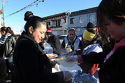 On a cold, blustery New Year's morning, volunteers working with Gerardo Maldonado help serve tacos and hot beverages to the needy on the corner of Soledad Street and Market Way in Salinas.