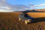 My Nissan Xterra and the lonely arc of tire tracks in the remote Smoke Creek Desert near Nevada Wilderness Study Areas.