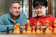 Chess pieces -- including the king and queen -- are pictured as American chess prodigy Awonder Liang, 13, gets ready to play a game with mentor, Dr. Dennis Doren, at Doren's home in Madison, Wis., on March 31, 2016. The middle-school student has already won several youth championships and earned the title of International Master. (Photo by Jeff Miller, www.jeffmillerphotography.com)