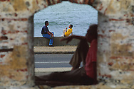 Un hombre y un niño al  fondo de la ventana disfrutan junto al mar de una conversación. Mientras un anciano descansa sobre una de las ventanas de las muralla. Cartagena de Indias, 2001 (Ramón Lepage / Orinoquiaphoto)      The fortified wall of Cartagena is in excellent condition and stretches more-or-less unbroken round a good portion of the Old Town. It is a pleasure for locals well as visitors to walk and observe the colonial architecture and excellent view of the Caribbean ocean..